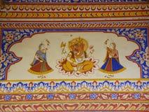 Φωτεινά χρώματα Ganesha και των χορεύοντας κοριτσιών, τέχνη τοίχων στην παλαιά οικοδόμηση του Rajasthan στοκ εικόνες