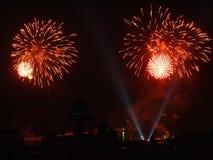 Φωτεινές εκρήξεις των πυροτεχνημάτων στο νυχτερινό ουρανό που καταβρέχει τους εκστατικούς θεατές στα κεφάλια τους που απολαμβάνου Στοκ Εικόνες