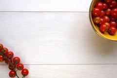 Φωτεινές κόκκινες juicy ντομάτες σε ένα κίτρινο κύπελλο στο ξύλο Στοκ εικόνες με δικαίωμα ελεύθερης χρήσης