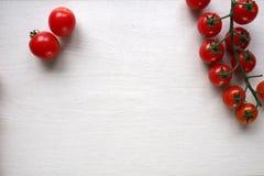 Φωτεινές κόκκινες juicy ντομάτες στο άσπρο ξύλινο υπόβαθρο Στοκ Φωτογραφίες