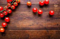 Φωτεινές κόκκινες juicy ντομάτες στο κατασκευασμένο ξύλινο υπόβαθρο Στοκ φωτογραφία με δικαίωμα ελεύθερης χρήσης