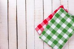 Φωτεινές πετσέτες κουζινών στις άσπρες χρωματισμένες ξύλινες σανίδες στοκ εικόνες