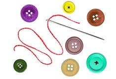 Φωτεινές ράβοντας κουμπιά και βελόνα με το νήμα που απομονώνεται στο λευκό στοκ εικόνες με δικαίωμα ελεύθερης χρήσης