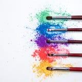 Φωτεινές σκιές ματιών στα διαφορετικά χρώματα του ουράνιου τόξου και των βουρτσών για τα καλλυντικά σε ένα άσπρο υπόβαθρο στοκ εικόνα με δικαίωμα ελεύθερης χρήσης