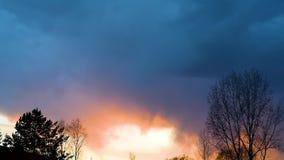 Φωτεινή ηλιοβασίλεμα ή ανατολή σε έναν σκοτεινό ουρανό με τα thunderclouds απόθεμα βίντεο
