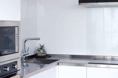 Φωτεινή και ευρύχωρη μοντέρνη κουζίνα με τις νέες συσκευές στοκ φωτογραφίες