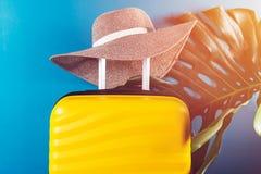 Φωτεινή και μοντέρνη βαλίτσα μεγέθους καμπινών με το καπέλο αχύρου και το φύλλο monstera στοκ φωτογραφία με δικαίωμα ελεύθερης χρήσης
