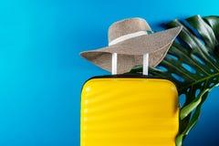 Φωτεινή και μοντέρνη βαλίτσα μεγέθους καμπινών με το καπέλο αχύρου και το φύλλο monstera στοκ εικόνα με δικαίωμα ελεύθερης χρήσης