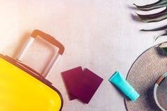 Φωτεινή και μοντέρνη βαλίτσα μεγέθους καμπινών με το καπέλο αχύρου, sunscreen και τα διαβατήρια στοκ φωτογραφία με δικαίωμα ελεύθερης χρήσης