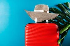 Φωτεινή και μοντέρνη βαλίτσα μεγέθους καμπινών με το καπέλο αχύρου και το φύλλο monstera στοκ φωτογραφίες με δικαίωμα ελεύθερης χρήσης