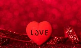 Φωτεινή καρδιά με την αγάπη επιγραφής, λάμποντας κόκκινη κορδέλλα στο φωτεινό κόκκινο υπόβαθρο στοκ εικόνες με δικαίωμα ελεύθερης χρήσης