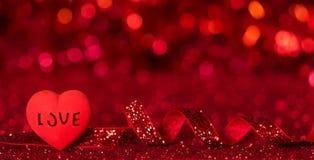Φωτεινή καρδιά με την αγάπη επιγραφής, λάμποντας κόκκινη κορδέλλα στο φωτεινό κόκκινο υπόβαθρο στοκ εικόνες