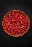 Φωτεινή κόκκινη σταφίδα σε ένα ξύλινο καλάθι σε ένα μαύρο υπόβαθρο Ζωηρόχρωμο κόκκινο ρεύμα Μια τοπ άποψη του ώριμου και νόστιμου στοκ φωτογραφία