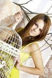 Φωτεινή νέα όμορφη τοποθέτηση γυναικών με ένα κλουβί Στοκ φωτογραφία με δικαίωμα ελεύθερης χρήσης