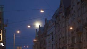 Φωτεινή πανσέληνος ορατή στις οδούς πόλεων που χρησιμοποιούν τον τηλε φακό φωτογραφιών με τα φω'τα πόλεων στο πρώτο πλάνο και τη  φιλμ μικρού μήκους