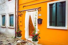 Φωτεινή πορτοκαλιά πρόσοψη του σπιτιού με τα λουλούδια στα δοχεία και τις άσπρες κουρτίνες στη Βενετία, Ιταλία στοκ εικόνες