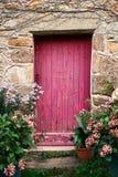 Φωτεινή ρόδινη ξύλινη πόρτα χρωμάτων στο παλαιό πέτρινο σπίτι Στοκ Εικόνες