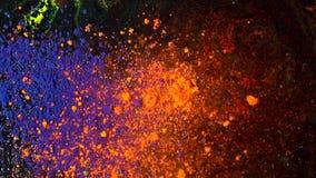 Φωτεινή χρωματισμένη έκρηξη σκόνης σε ένα μαύρο υπόβαθρο, έννοια τέχνης Κίνηση των μπλε και πορτοκαλιών μελανιών σκονών, πολύχρωμ φιλμ μικρού μήκους