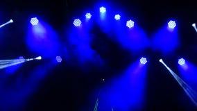 Φωτεινοί λάμποντας λέιζερ και καπνός επικέντρων συναυλίας στο υπόβαθρο σκηνής φιλμ μικρού μήκους