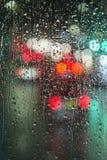 Φωτεινοί σηματοδότες που βλέπουν μέσω ενός βροχερού πλακακιού γυαλιού στοκ εικόνες