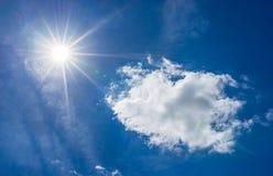 Φωτεινός λάμποντας ήλιος στο νεφελώδη μπλε ουρανό Στοκ Εικόνες