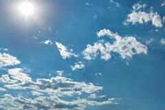 Φωτεινός ήλιος, άσπρα σύννεφα σωρών και φωτεινός ήλιος στο μπλε ουρανό Στοκ Φωτογραφία