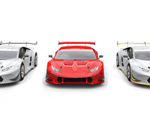 Φωτεινός κόκκινος supercar με τα άσπρα sportscars σε κάθε πλευρά Στοκ φωτογραφία με δικαίωμα ελεύθερης χρήσης