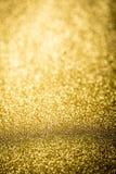 Φωτεινός μέσω του χρυσού αφηρημένου υποβάθρου bokeh εστίασης Στοκ Εικόνες