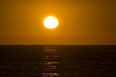 Φωτεινός πορτοκαλής ήλιος πέρα από τον ωκεανό Στοκ Φωτογραφία