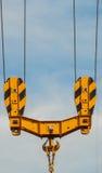 Φωτεινός πορτοκαλής γερανός πύργων ενάντια του μπλε ουρανού, λεπτομέρεια γάντζων, έννοια κατασκευής Στοκ φωτογραφία με δικαίωμα ελεύθερης χρήσης
