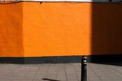 Φωτεινός πορτοκαλής τουβλότοιχος σε ένα πεζοδρόμιο Στοκ Εικόνα