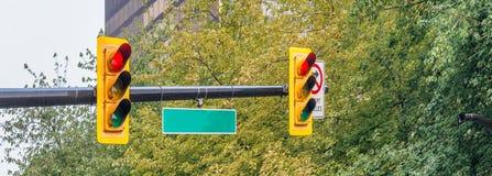 Φωτεινός σηματοδότης κατά μήκος του πάρκου πόλεων με το κενό σημάδι οδών Στοκ Εικόνες