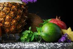 Φωτεινό αβοκάντο, ώριμος γρανάτης, ανανάς, καρύδα και carambola Χαριτωμένες λουλούδια και μέντα Κινηματογράφηση σε πρώτο πλάνο τω Στοκ φωτογραφία με δικαίωμα ελεύθερης χρήσης