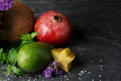 Φωτεινό αβοκάντο, ώριμος γρανάτης, καρύδα και carambola Χαριτωμένες λουλούδια και μέντα Κινηματογράφηση σε πρώτο πλάνο των φρούτω Στοκ Φωτογραφίες