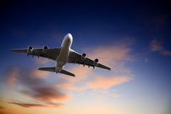 φωτεινό αεριωθούμενο αεροπλάνο αεροπλάνων από τον ουρανό που παίρνει το λυκόφως Στοκ εικόνα με δικαίωμα ελεύθερης χρήσης