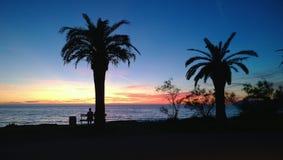 Φωτεινό ηλιοβασίλεμα στη μαυροβούνια ακτή στο φραγμό Σκιαγραφίες των φοινίκων και μια συνεδρίαση ατόμων σε έναν πάγκο στην ακτή Στοκ εικόνα με δικαίωμα ελεύθερης χρήσης