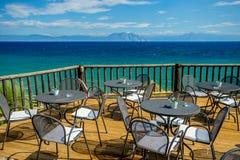 Φωτεινό ηλιόλουστο απόγευμα στο ξύλινο πεζούλι με την άποψη της τυρκουάζ Μεσογείου και των απόμακρων βουνών στοκ φωτογραφίες με δικαίωμα ελεύθερης χρήσης
