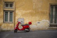 Φωτεινό κόκκινο μηχανικό δίκυκλο Vespa σε μια αστική οδό Στοκ εικόνα με δικαίωμα ελεύθερης χρήσης