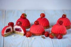 Φωτεινό κόκκινο mousse κέικ με τη διακόσμηση φραουλών σε ένα μπλε ξύλινο υπόβαθρο Στοκ εικόνα με δικαίωμα ελεύθερης χρήσης