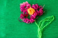 Φωτεινό λουλούδι φιαγμένο από νήματα στο πράσινο υπόβαθρο Στοκ Εικόνες