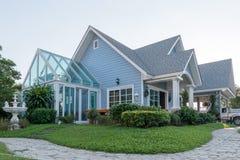 Φωτεινό μπλε σπίτι στο sunlght με τις ζωηρόχρωμες παπαρούνες και κάποιο grac Στοκ Εικόνες