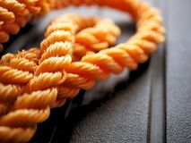 Φωτεινό πλεγμένο πορτοκάλι νάυλον σχοινί στο μπλεγμένο μαύρο υπόβαθρο σπειρών στοκ εικόνες