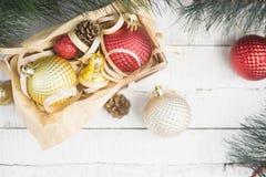 Φωτεινό υπόβαθρο Χριστουγέννων με τα κόκκινα και χρυσά παιχνίδια Χριστουγέννων στο κιβώτιο Στοκ Φωτογραφία