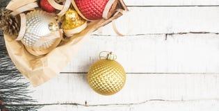 Φωτεινό υπόβαθρο Χριστουγέννων με τα κόκκινα και χρυσά παιχνίδια Χριστουγέννων στο κιβώτιο στον ξύλινο πίνακα Στοκ Εικόνες