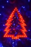 Φωτεινό χριστουγεννιάτικο δέντρο παιχνιδιών στο μπλε χριστουγεννιάτικο δέντρο Στοκ εικόνα με δικαίωμα ελεύθερης χρήσης