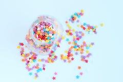 Φωτεινό χρωματισμένο ψέκασμα βιομηχανιών ζαχαρωδών προϊόντων των αστεριών σε ένα βάζο γυαλιού σε ένα ελαφρύ υπόβαθρο Μαλακή εστία στοκ εικόνες