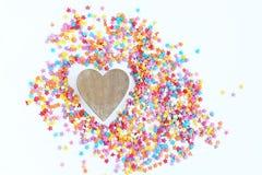 Φωτεινό χρωματισμένο ψέκασμα βιομηχανιών ζαχαρωδών προϊόντων των αστεριών και της ξύλινης καρδιάς σε ένα ελαφρύ υπόβαθρο, μαλακή  Στοκ φωτογραφίες με δικαίωμα ελεύθερης χρήσης
