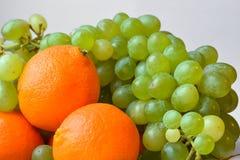 Φωτεινό tangerine και μια μεγάλη δέσμη των πράσινων σταφυλιών Στοκ Εικόνες