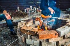 Φωτιά πυρών προσκόπων - άνθρωποι που ψήνουν τα λουκάνικα Στοκ Εικόνα
