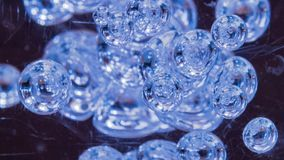 Φωτισμένες μπλε φυσαλίδες που επιπλέουν στο σαφές υγρό που βλέπει μέσω του γρατσουνισμένης παραθύρου ή της παραφωτίδας αφηρημένη  στοκ φωτογραφίες